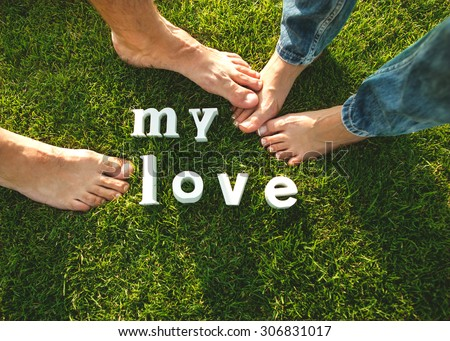 couple standing barefoot in the grass, the concept of love. Valentine's Day - stock photo