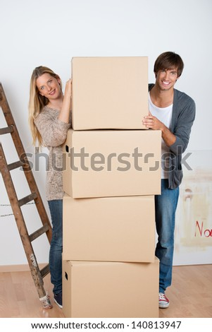 couple standing beneath a batch of boxes - stock photo