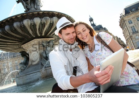 Couple standing by the Place de la Bourse with electronic tablet - stock photo