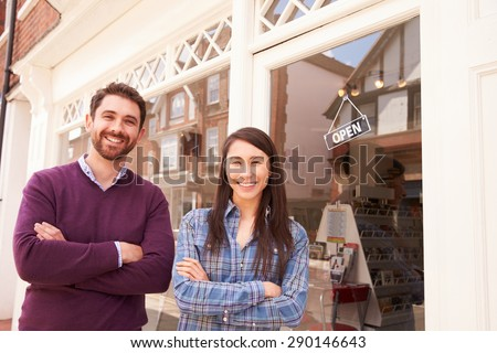 Couple standing in front of a shop window - stock photo