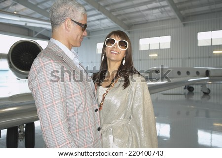 Couple standing in front of airplane in a hanger - stock photo