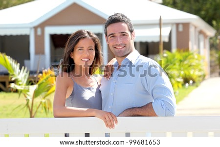 Couple standing in front of new home - stock photo