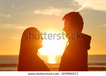 Couple standing looking each other and falling in love with the sun in the middle at sunset in the beach - stock photo