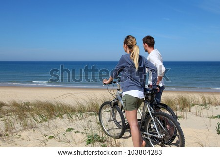 Couple standing on a sand dune with bicycles - stock photo