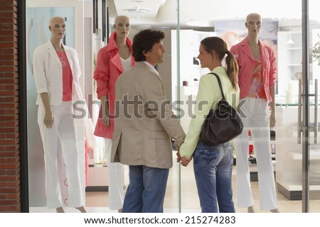Couple standing outside clothes shop in front of window display, holding hands, smiling, rear view - stock photo