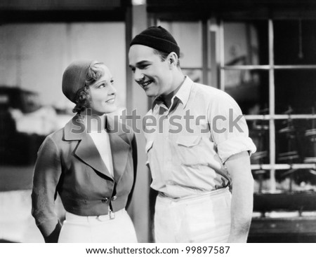 Couple standing together and smiling - stock photo