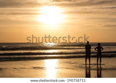 Couple Stands During Romantic Sunset on Costa Rican Beach - stock photo