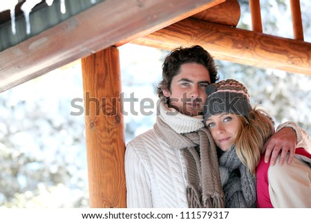 Couple stood by their holiday chalet - stock photo