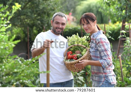 Couple stood in garden with vegetables - stock photo