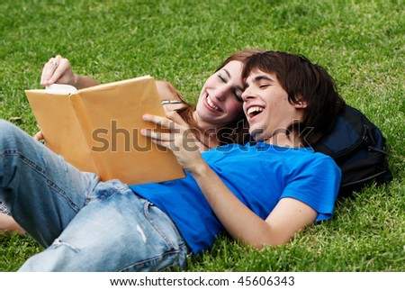 Couple students laying on the grass and reading a book - stock photo