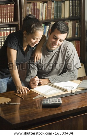 Couple studies in library. There are books and tools on the table and they are leaning against each other. Vertically framed photo. - stock photo