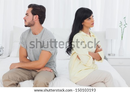 Couple sulking with arms crossed in bedroom - stock photo