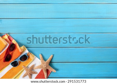 Couple sunbathing beach background, sunglasses, blue decking, copy space - stock photo
