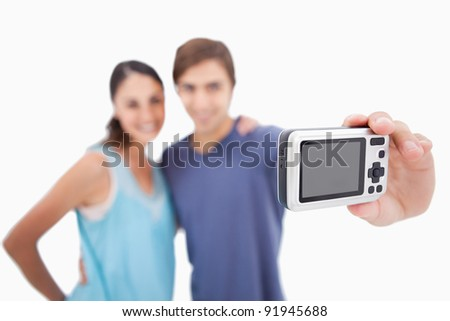 Couple taking a photo of themselves against a white background - stock photo