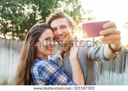 Couple taking a selfie with their cellphone outside - stock photo