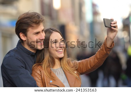 Couple taking selfie photo with a smart phone in the street with an unfocused background - stock photo