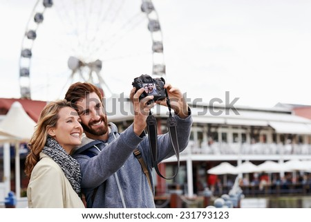 couple taking selfie picture photo at ferris wheel on vacation - stock photo