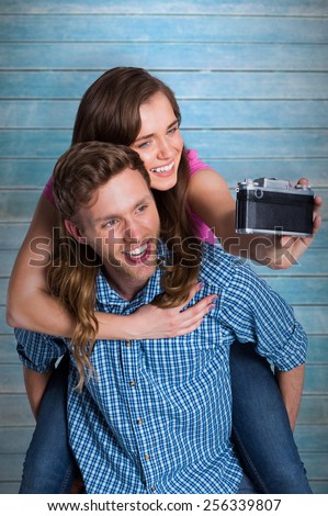 Couple taking selfie with digital camera against wooden planks - stock photo
