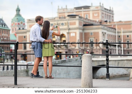 Couple taking smartphone photos in Stockholm city. Young adults tourists walking in the city of Stockholm during summer and taking selfies or pictures of the town. - stock photo