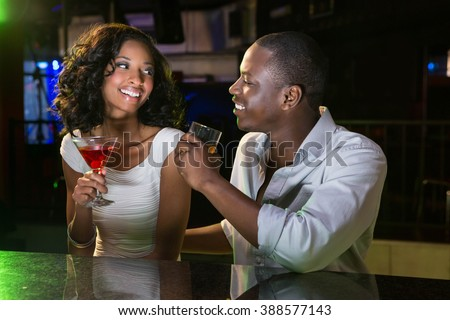 Couple talking and smiling while having drinks at bar counter in bar - stock photo