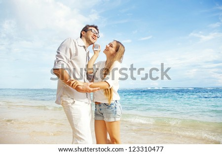 couple talking by phone on beach - stock photo