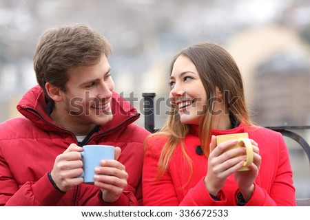 Couple talking relaxed sitting on a bench with coffee cups in winter - stock photo