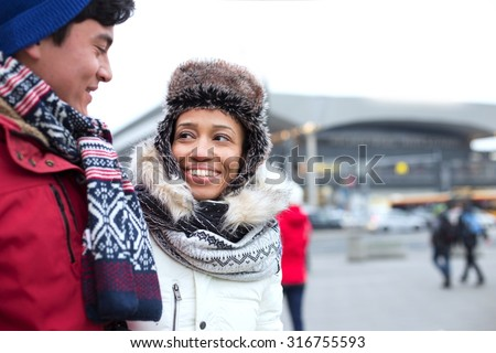 Couple talking while walking in city during winter - stock photo
