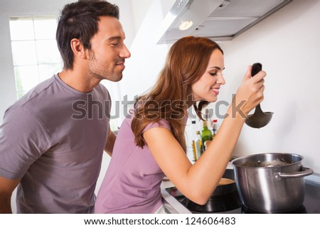 Couple tasting their dinner in kitchen - stock photo