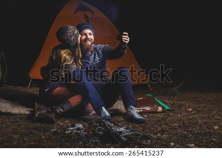 Couple tent camping in the wilderness taking selfie - stock photo