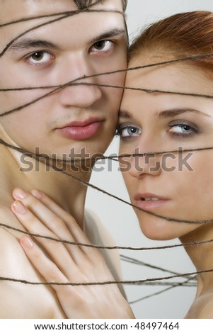 Couple tied together in love with thread - stock photo