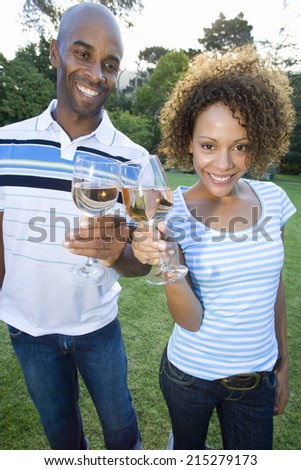Couple toasting glasses outdoors, smiling, close-up - stock photo