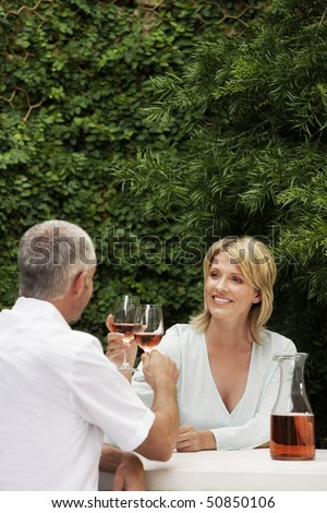 Couple toasting with wine glasses, sitting outdoors - stock photo