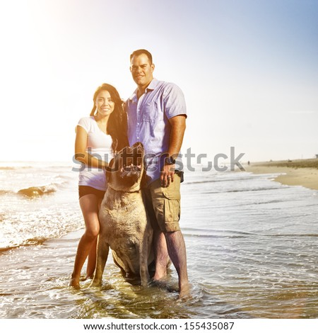 couple together with pet dog posing on the beach. - stock photo