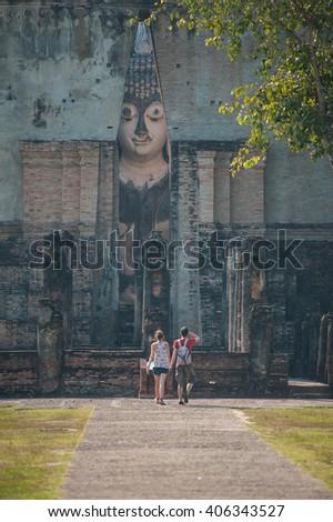 Couple tourist blessing big Buddha at Srichum temple in Sukhothai historical park, Thailand,  Asia - stock photo