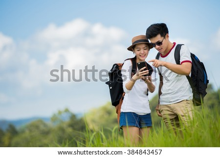 Couple tourists opening the map tourist women she is open to a GPS smartphone. - stock photo
