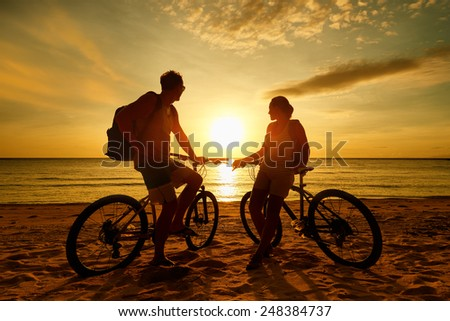 Couple tourists with Bicycles Watching Sunset. Summer Nature Background with Beautiful Sky and Sea. Active Leisure Concept. - stock photo