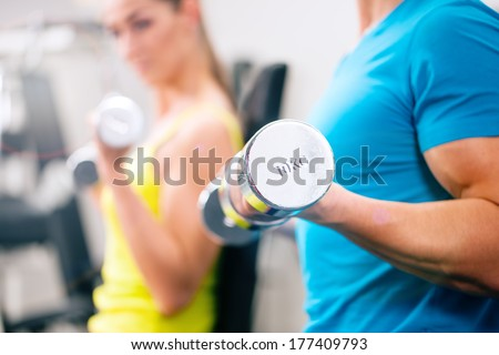 Couple training for fitness in gym with weights - stock photo