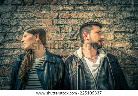 Couple turning heads in opposite directions - Two persons ignoring themselves after argument - Unhappy lovers - stock photo
