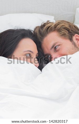 Couple under the quilt looking at each other in their bed - stock photo