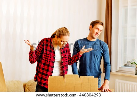 Couple unpaking boxes, stressed woman looking to inside  - stock photo