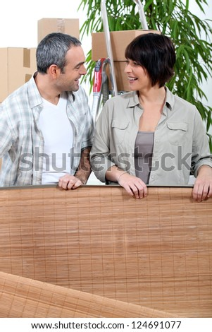 Couple unrolling a mat in their new home - stock photo