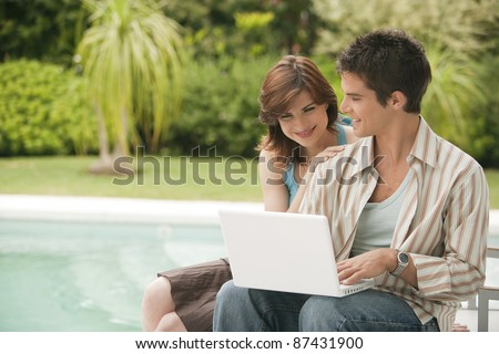 Couple using a laptop by swimming pool, hotel exterior. - stock photo