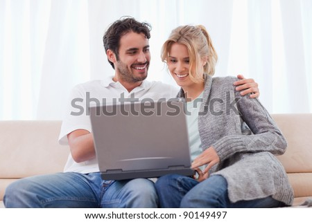 Couple using a notebook in their living room - stock photo