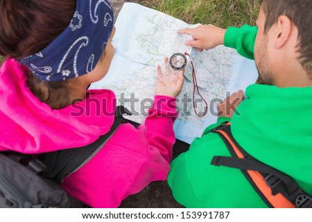 Couple using compass and map on their hike in the country - stock photo