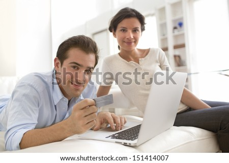 Couple using credit card to shop on line. Laptop.indoor on sofa - stock photo