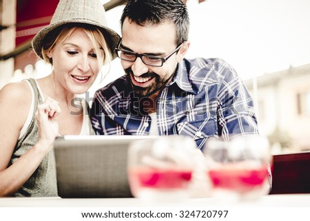 Couple using digital technology in a bar - stock photo