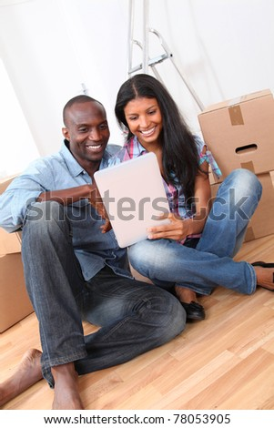 Couple using electronic tablet in their new house - stock photo