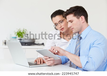 Couple Using Laptop And Digital Tablet At Home - stock photo