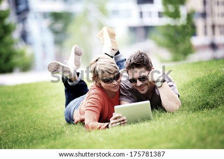 Couple using laptop in city park (lomo efect) - stock photo
