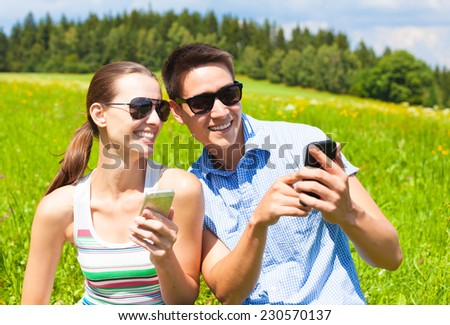 Couple using mobile cellphone in the park - stock photo